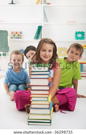 Happy schoolchildren with stack of books sitting in classroom