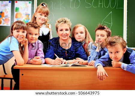 Happy schoolchildren with their teacher at a classroom. Education. - stock photo