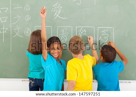 happy schoolgirl after writing chinese on blackboard - stock photo