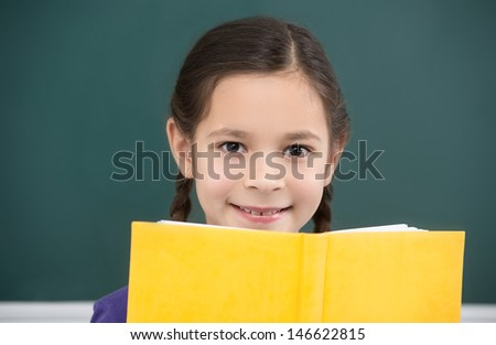 Happy schoolgirl.  Cheerful little schoolgirl looking out from the textbook while standing in front of blackboard - stock photo