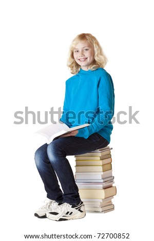 Happy schoolgirl holding book and sitting on school books. Isolated on white background. - stock photo