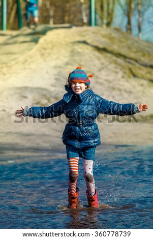 Happy schoolgirl jumping in the deep puddle at the autumn playground - stock photo