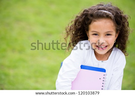Happy schoolgirl outdoors carrying notebooks and smiling - stock photo