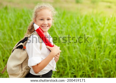 happy schoolgirl standing near the house at the day time and ready to go to school - stock photo