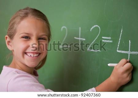 Happy schoolgirl writing a number on a blackboard - stock photo