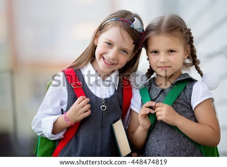 Happy schoolgirls are going to school - stock photo