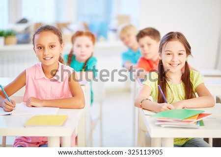 Happy schoolgirls looking at camera while sitting by desks at lesson - stock photo