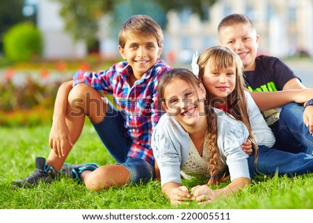 happy schoolkids playing in the park - stock photo