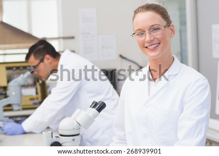 Happy scientist smiling at camera in the laboratory - stock photo