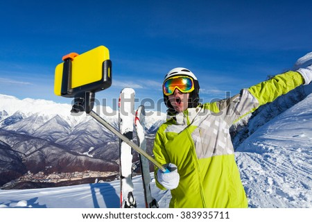 Happy screaming skier take photo with camera - stock photo