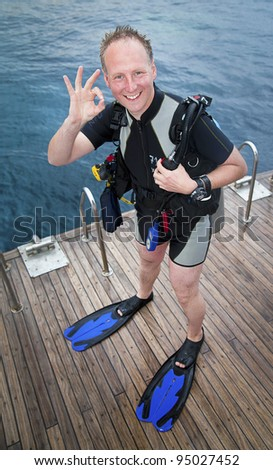 Happy scuba diver with professional equipment just after diving - stock photo