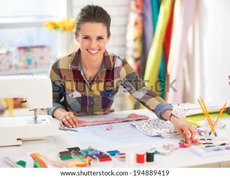 Happy seamstress working in studio - stock photo