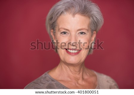 Happy seior woman in front of red background - stock photo