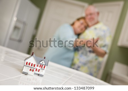 Happy Senior Adult Couple Dancing Together and Gazing Over Small Model Home on Their Kitchen Counter. - stock photo
