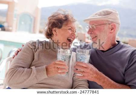 Happy Senior Adult Couple Enjoying Drinks Together. - stock photo