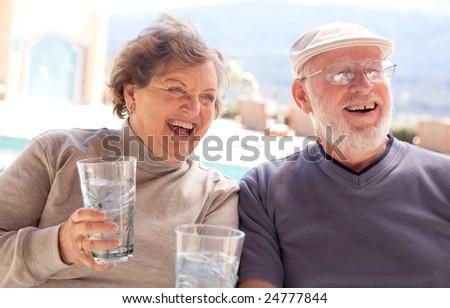 Happy Senior Adult Couple Enjoying Drinks Together. - stock photo