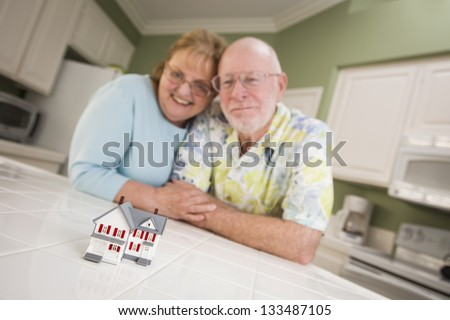 Happy Senior Adult Couple Gazing Over Small Model Home on Their Kitchen Counter. - stock photo