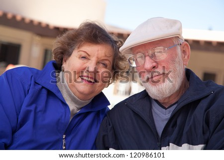 Happy Senior Adult Couple Portrait Bundled Up Outdoors. - stock photo