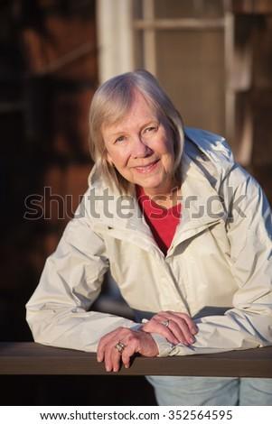 Happy senior adult female leaning on railing outdoors - stock photo