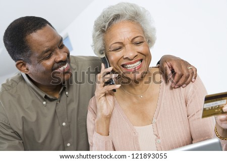 Happy senior African American woman on call while holding credit card with man besides her - stock photo