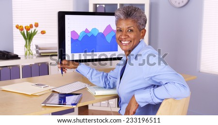 Happy senior african businesswoman sitting at desk - stock photo