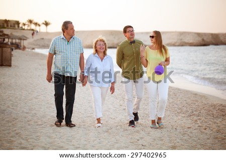Happy senior and young couples having a walk at the seaside. Parents and adult children together outdoor - stock photo