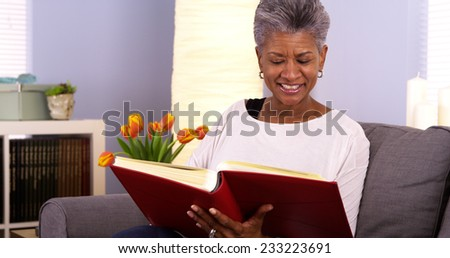 Happy senior black woman looking though photo album - stock photo