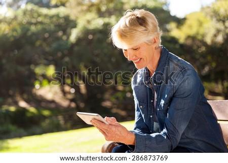 happy senior blond woman texting on smart phone - stock photo