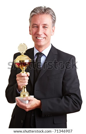 Happy senior business man holding a trophy in his hands - stock photo