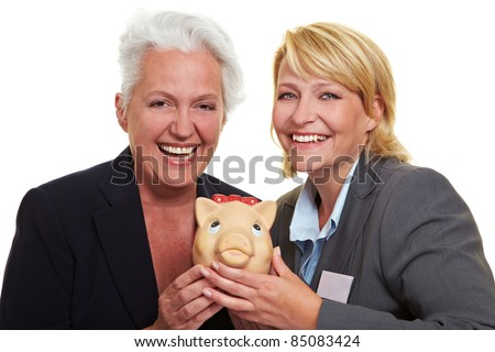 Happy senior business woman with piggy bank and colleague - stock photo
