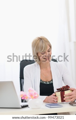 Happy senior business woman with present at work
