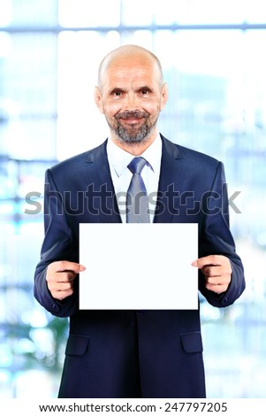 Happy senior businessman holding Blank business card in the office - stock photo