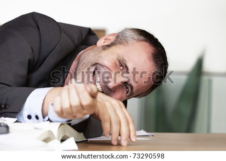 Happy senior businessman in dark suit sitting at desk and laughing hearty. - stock photo