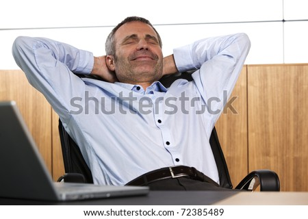 Happy senior businessman leaning back in his office chair. - stock photo