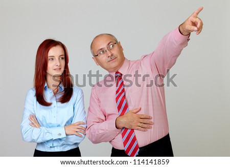 Happy senior businessman pointing something to young attractive businesswoman in shirts, isolated on grey - stock photo