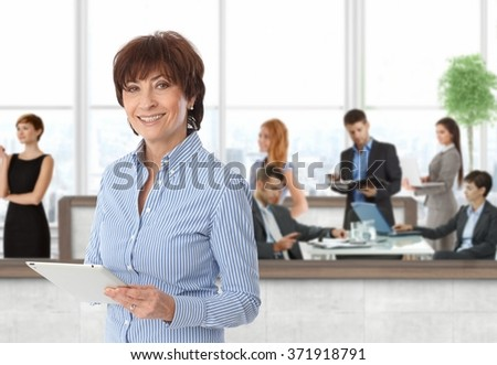 Happy senior businesswoman with team of working businesspeople at office. - stock photo