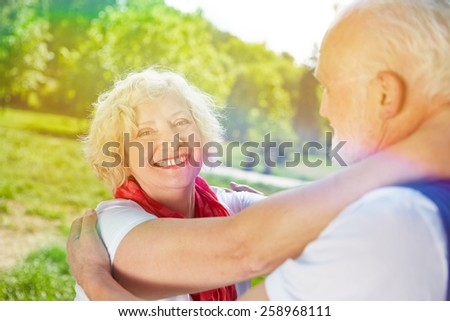 Happy senior caouple dancing together in summer in a park - stock photo