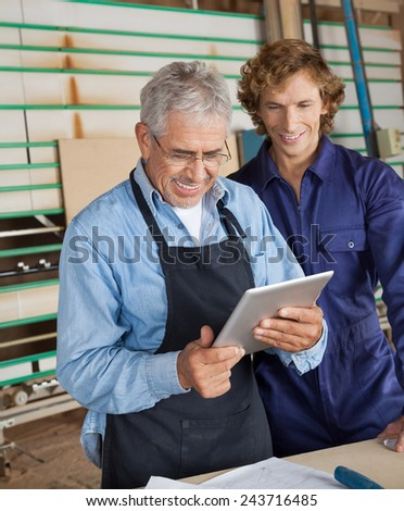 Happy senior carpenter using digital tablet with coworker in workshop - stock photo