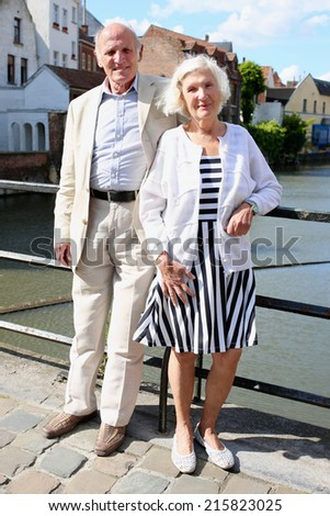 Happy senior caucasian couple traveling around Europe walking in the streets of medieval city Ghent, Belgium, enjoying scenes of the canals on a sunny day - active retirement concept - stock photo