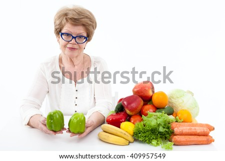 Happy senior Caucasian woman stretching hands with two green sweet peppers, vegetables and fruits are on table, white background - stock photo