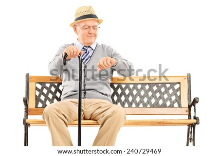 Happy senior checking the time seated on a bench isolated on white background - stock photo