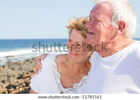 happy senior citizen couple hugging on beach - stock photo