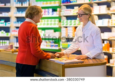 Happy senior citizen customer in red standing at pharmacy counter as pharmacist in eyeglasses and lab coat hands her a medication order - stock photo