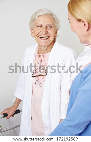 Happy senior citizen woman in nursing home with a nurse - stock photo