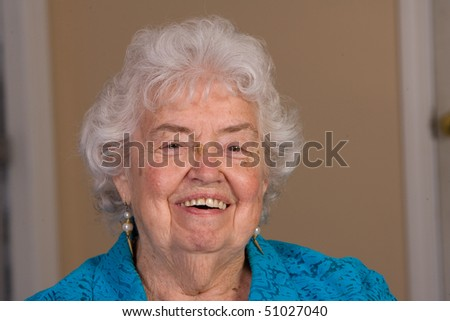 Happy senior citizen woman laughing in this closeup. - stock photo
