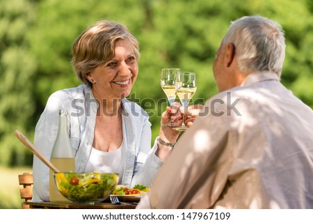 Happy senior citizens clinking glasses in garden