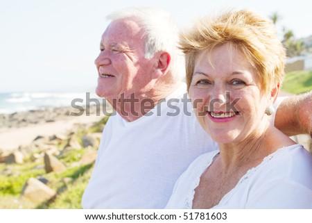 happy senior couple at beach on a sunny day - stock photo