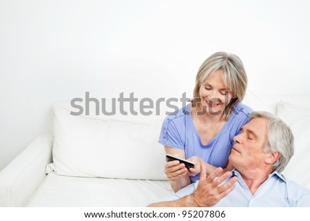 Happy senior couple at home playing with a smartphone - stock photo