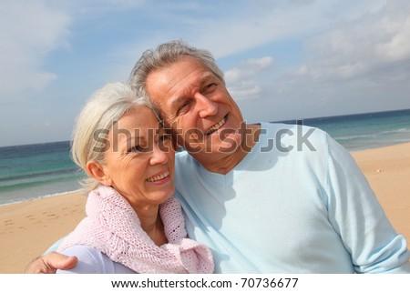 Happy senior couple at the beach - stock photo