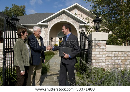 happy senior couple buying a new home from a real estate agent - stock photo